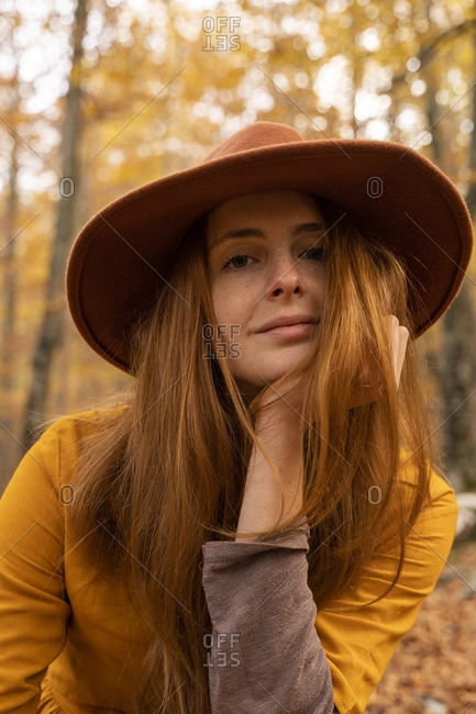Portrait of fashionable redheaded young woman in autumnal forest