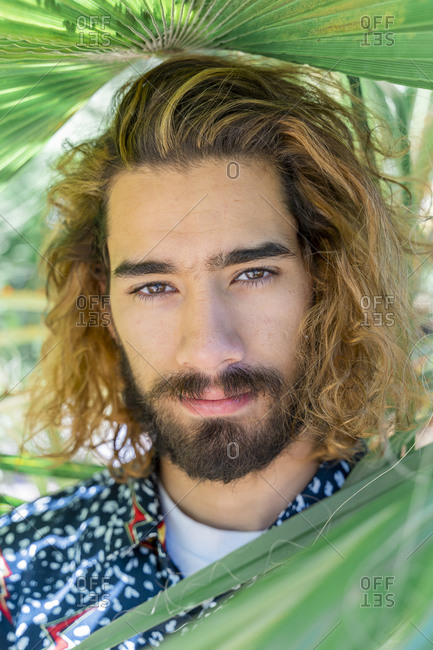 Portrait of bearded young man with dyed hair among palm leaves