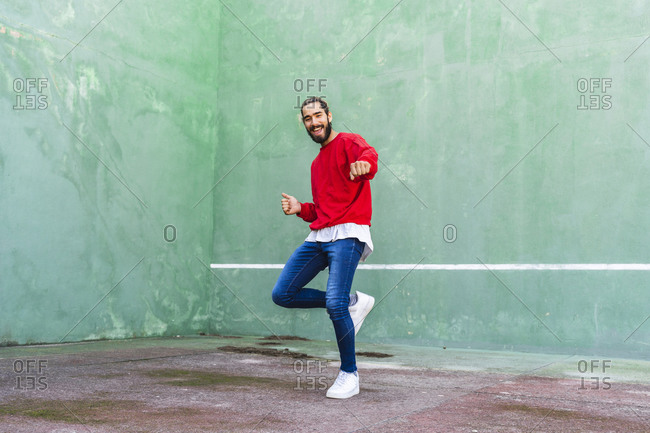 Portrait of bearded young man dancing in front of green wall