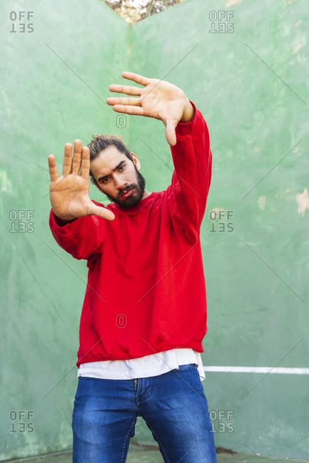 Portrait of serious young man wearing red sweatshirt raising hands in front of green wall