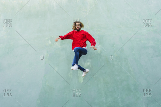 Portrait of young man wearing red sweatshirt jumping in the air in front of green wall