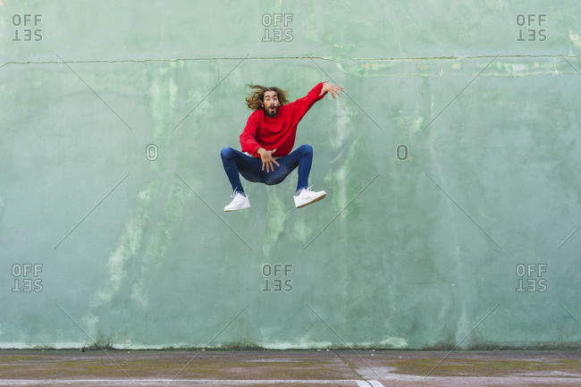 Portrait of young man in wearing red sweatshirt jumping in the air in front of green wall