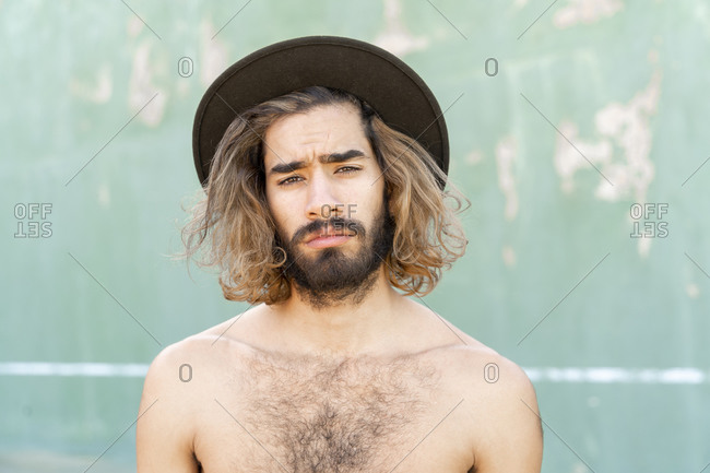 Portrait of shirtless young man wearing hat