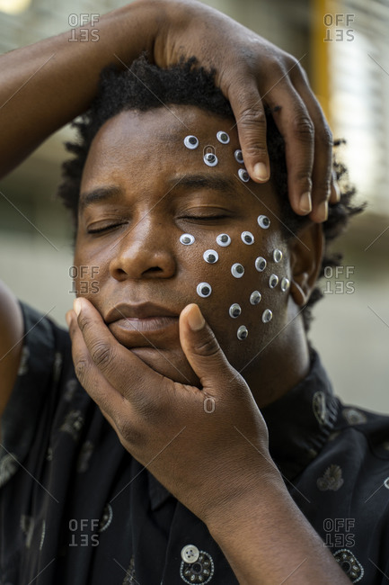 Man with sticky eyes on his face- closed eyes and hands