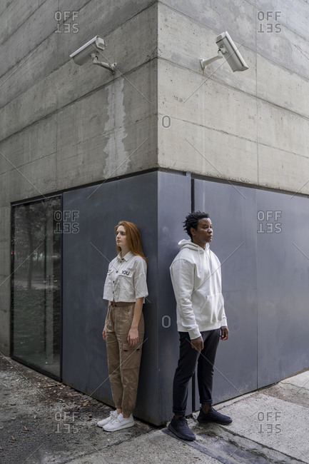 Man and woman leaning on a wall- security cameras hanging over their heads