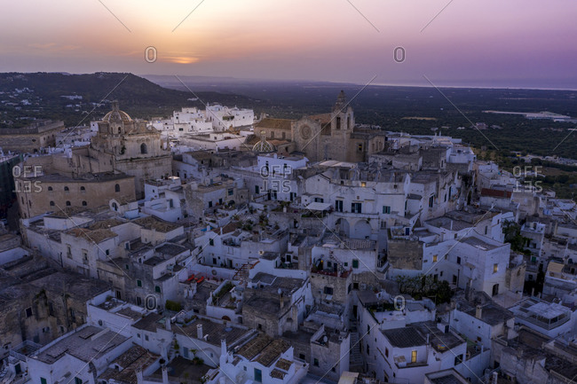 Italy- Province of Brindisi- Osuna- Aerial view of old town citadel at sunset