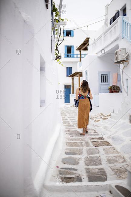 Woman walking through narrow lanes of Mykonos- Greece