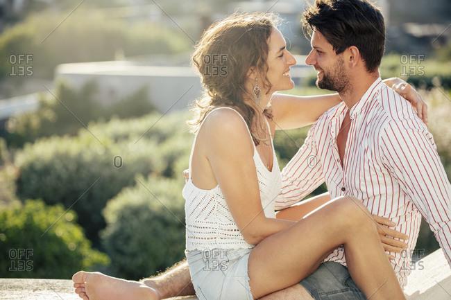Romantic couple sitting on wall- embracing- enjoying holidays