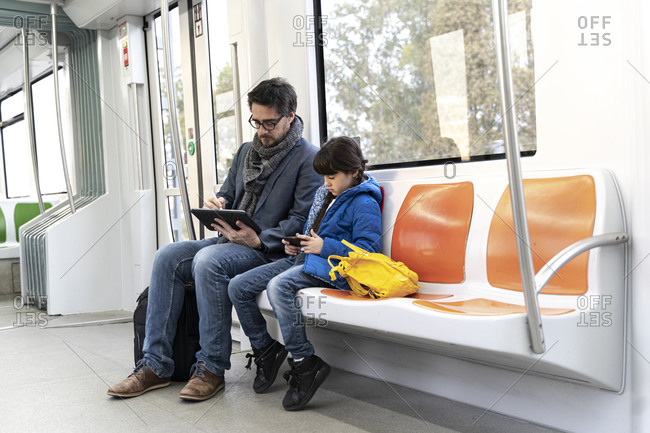 Father and daughter in metro and using tablet and smartphone