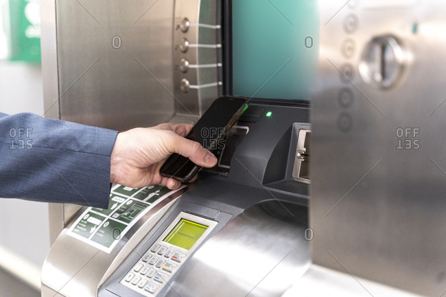 Man holding smartphone on ticket machine and paying