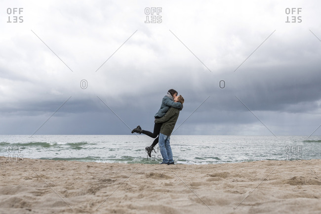 Russia- Kaliningrad Oblast- Zelenogradsk- Adult couple kissing on sandy coastal beach of Baltic Sea