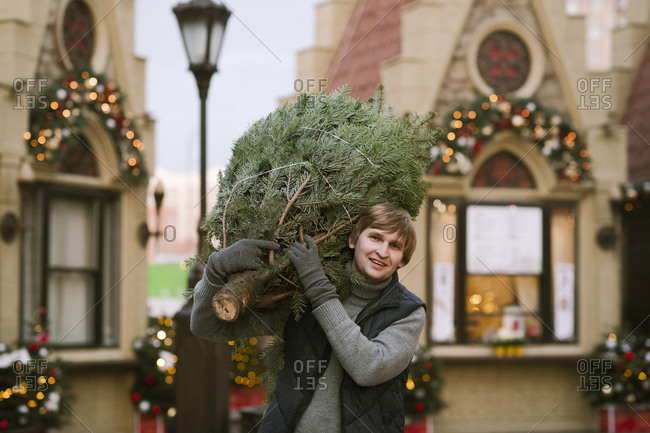 Smiling man with fir tree on his shoulder