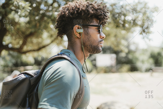 Young man with earphones in a park