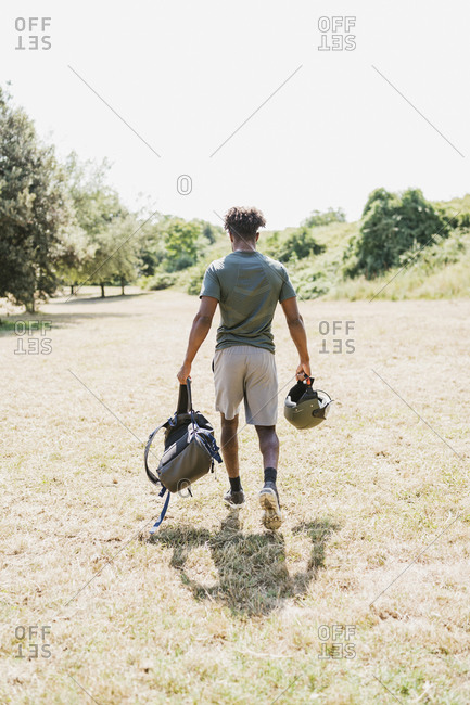 Rear view of young man with helmet and backpack walking in park