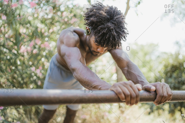 Young man during workout on bar in park