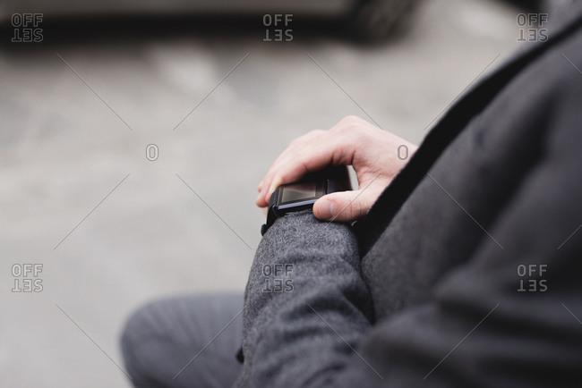 Crop view of businessman checking smartwatch