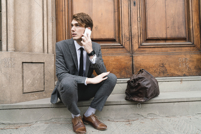 Portrait of young businessman on the phone sitting on steps of house entrance