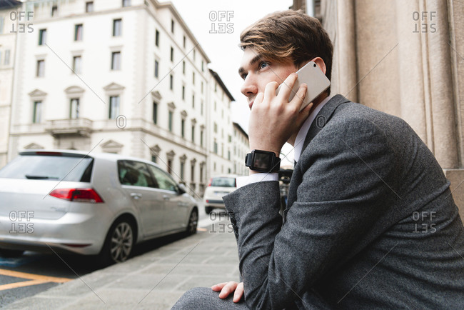 Young businessman with smartwatch on the phone in the city