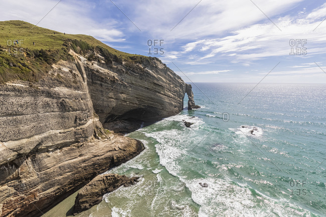 New Zealand- Cliffs and natural arch of Cape Farewell headland on sunny day