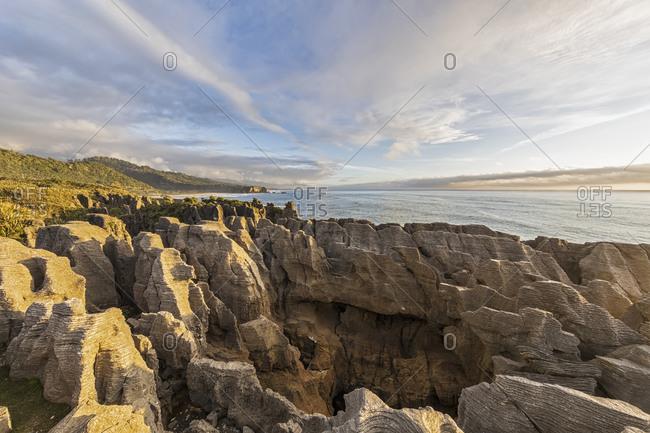 New Zealand- Buller District- Punakaiki- Limestone Pancake Rocks formation and coastal blow hole at dusk
