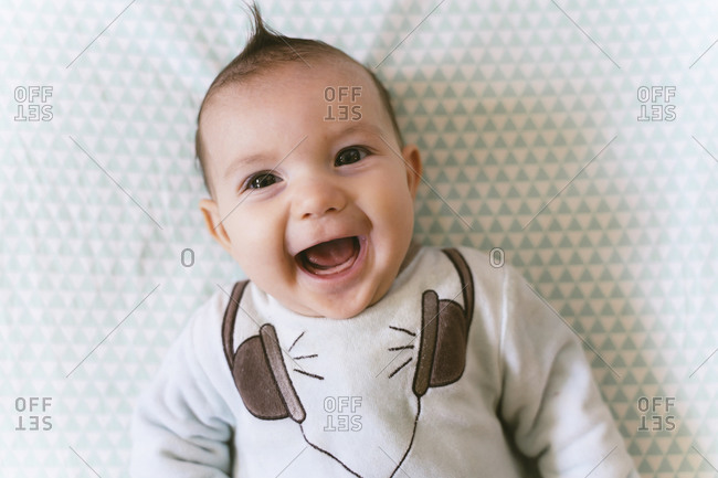 Portrait of laughing baby girl with appliqued headphones on pajama
