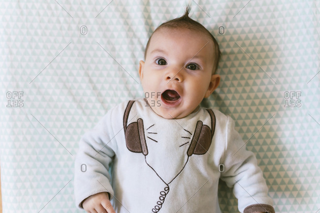Portrait of surprised baby girl with appliqued headphones on pajama