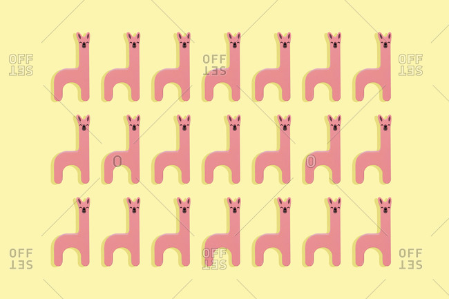 Cute pink llamas wooden toy in a row on yellow background
