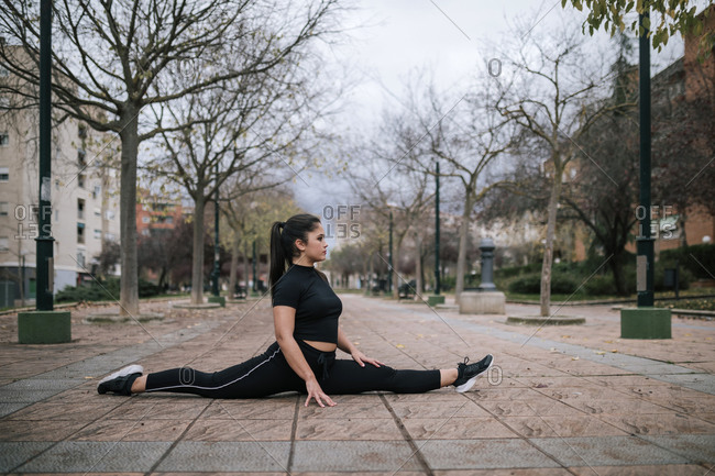 Young woman in black sportswear doing the splits on pavement