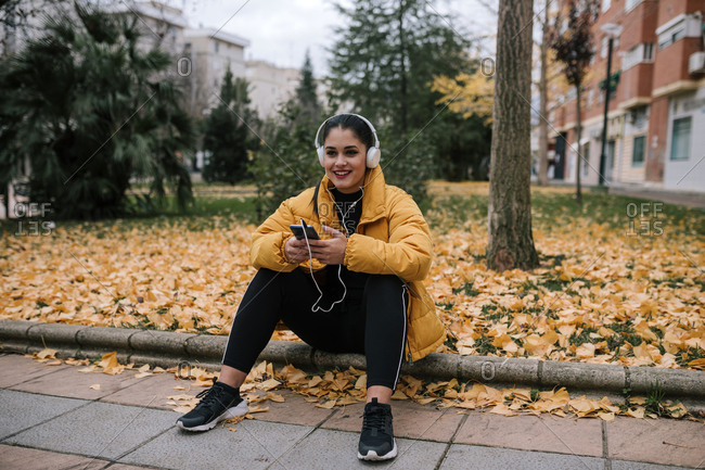 Portrait of smiling young woman listening music with headphones and smartphone in autumn