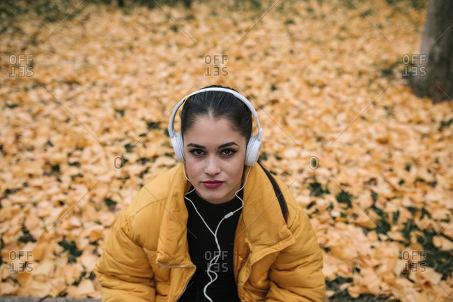 Portrait of young woman listening music with headphones in autumn