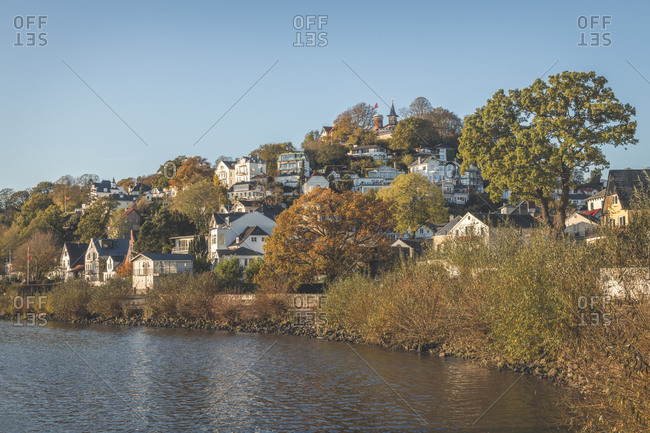 Germany- Hamburg- Suburb residences along bank of Elbe river in autumn