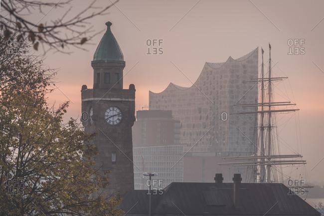 Germany- Hamburg- Landungsbrucken clock tower at dawn with Elbphilharmonie in background