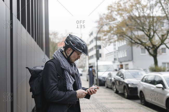 Young man with cycling helmet and backpack standing on pavement looking at cell phone