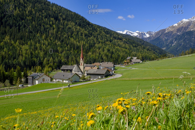 Italy- South Tyrol- Pens- Springtime meadow in front of mountain village in Penser Joch pass