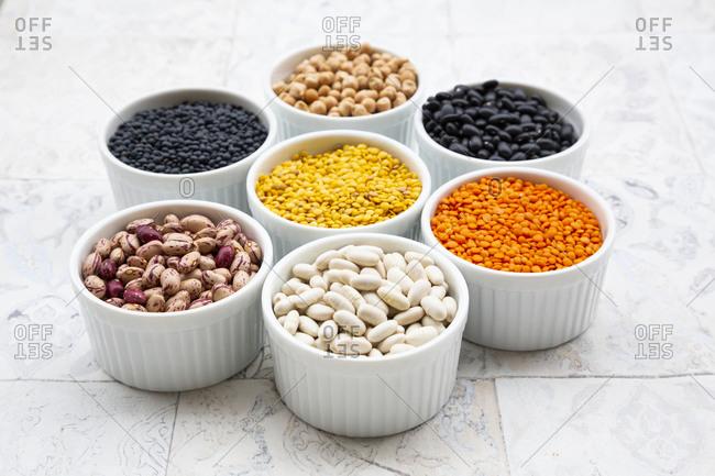 Various legumes in bowls: chickpeas- cannellini beans- quail beans- black beans- yellow lentils- red lentils- black lentils