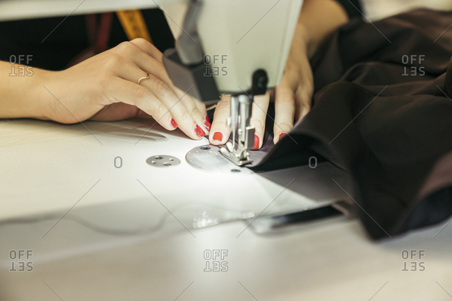 Young fashion designer using sewing machine- close-up