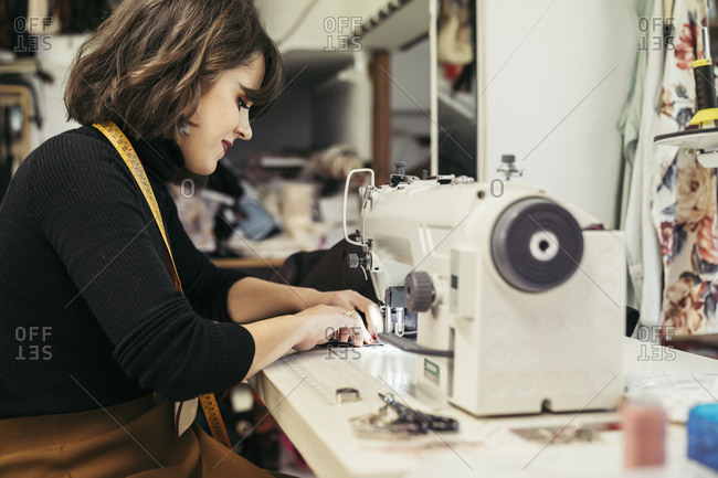 Young fashion designer using sewing machine