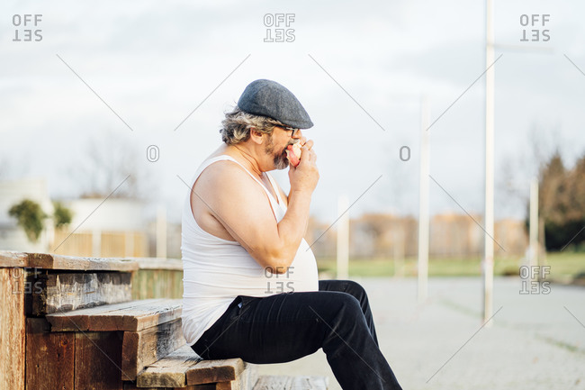Man with beer belly sitting on steps and eating a sandwich
