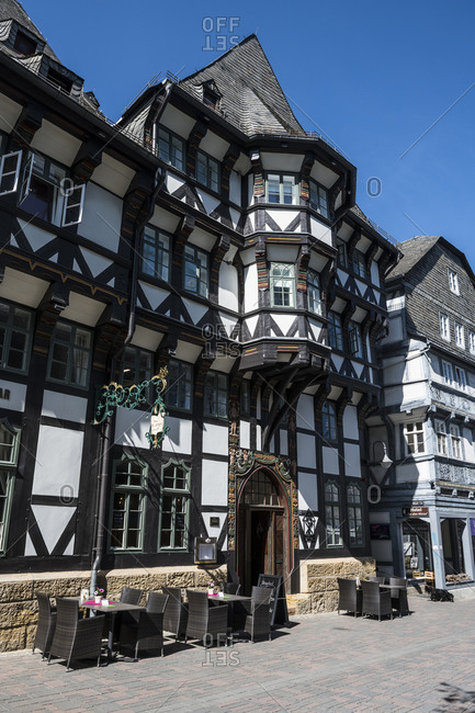 April 24, 2019: Germany- Lower Saxony- Goslar- Chairs and tables in front of half-timbered cafe in historical town