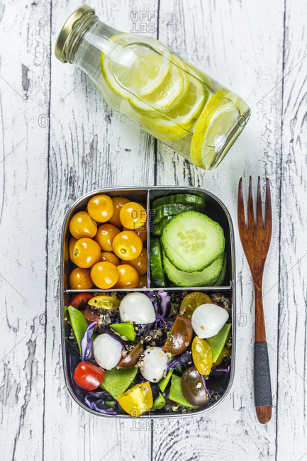Bottle of lemonade and lunchbox with cucumber slices- winter cherries and quinoa salad (quinoa- cherry tomato- red cabbage- sugar snap peas and mozzarella balls)