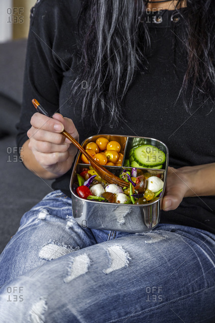 Mid section of woman sitting and eating from lunch box
