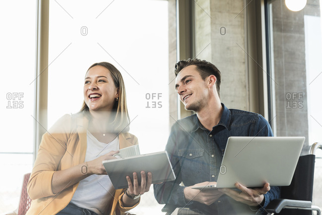 Happy young businessman with laptop in wheelchair and businesswoman with tablet in office