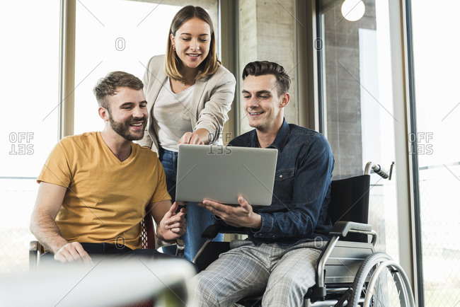 Young businessman in wheelchair showing laptop to colleagues in office
