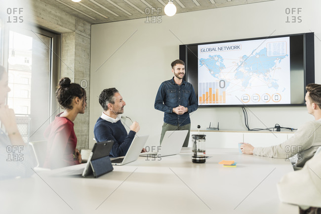 Young businessman leading a presentation in boardroom