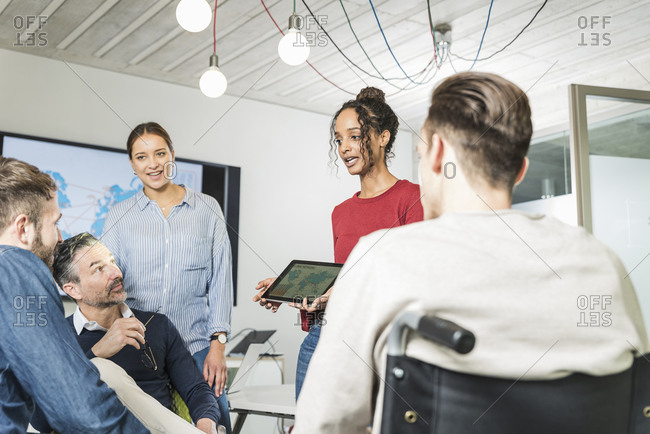 Young businesswoman sharing tablet with colleagues in office