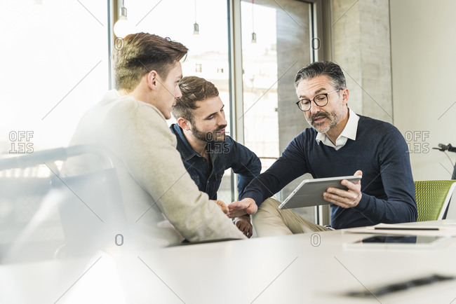 Three businessmen having a meeting in office sharing a tablet