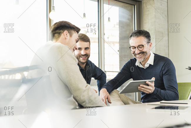 Three happy businessmen having a meeting in office sharing a tablet