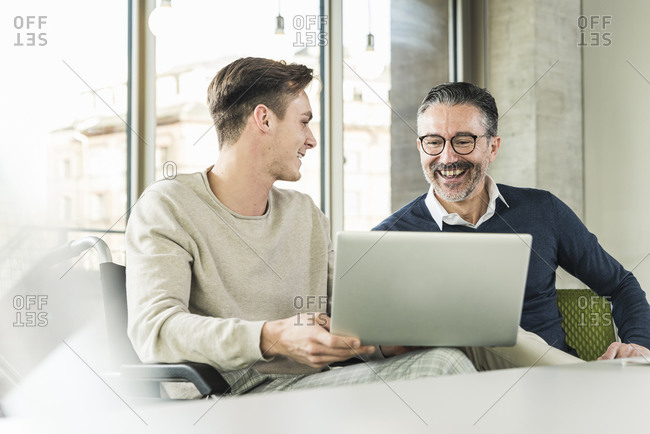 Happy mature businessman and young man in wheelchair using laptop in office