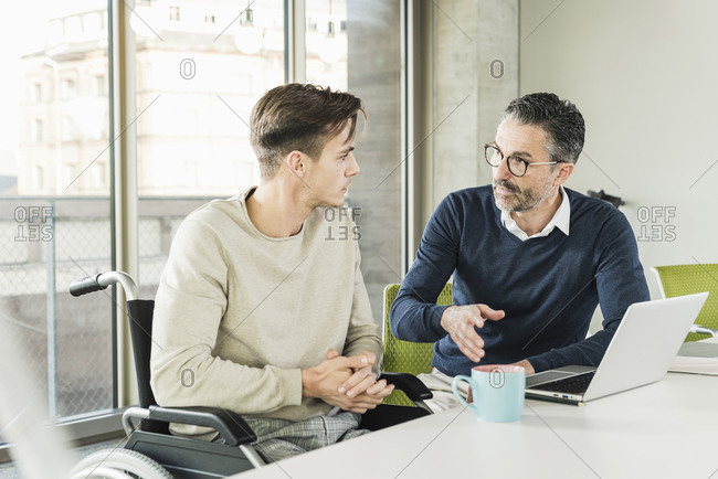 Mature businessman and young man in wheelchair talking at desk in office