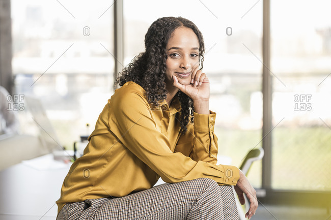 Portrait of smiling young businesswoman sitting on desk in office